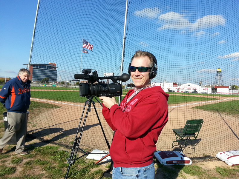 Director Jason Roche poses with his camera behind home plate in Oct. 2013.